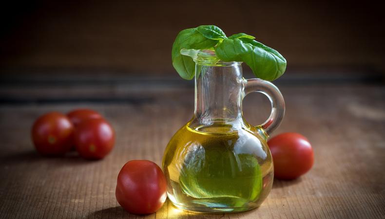 boccetta di olio aromatizzato al basilico su tavolino con pomodori