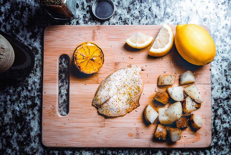 filetti di pesce branzino con fette di limone e zenzero