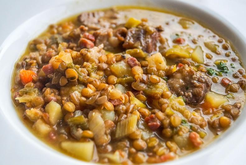 piatto di minestra con patate e lenticchie al pomodoro