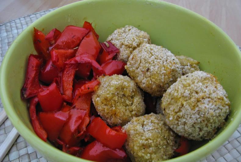 ciotola contenente polpette di lenticchie e miglio con peperoni rossi arrostiti