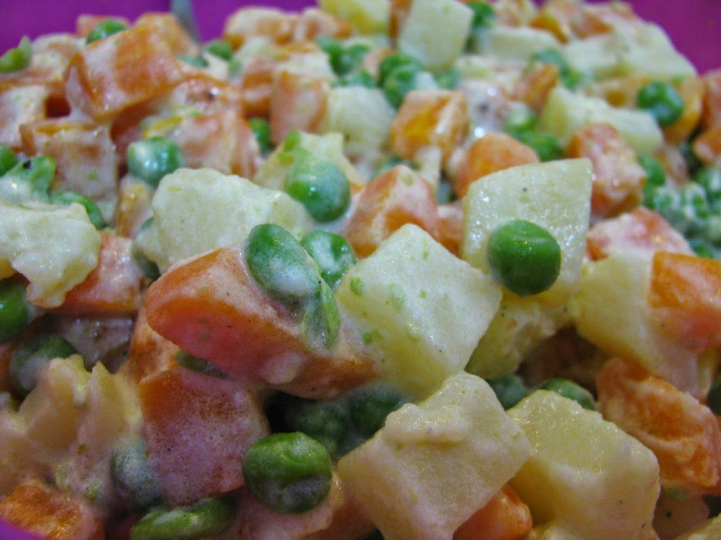 piatto di insalata russa condita con dello yogurt bianco
