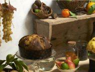 panettone artigianale in una cucina di campagna con frutta di stagione sul tavolo e grappoli di uva appesa