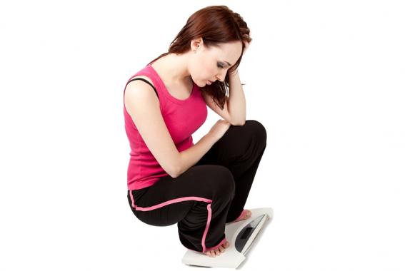 donna si pesa disperata su una bilancia