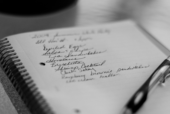 foto in bianco e nero di un quaderno con la lista della spesa