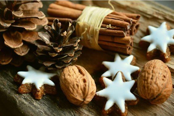 stecca di cannella su un tavolo con pigne, noci a guscio e biscotti a forma di stella