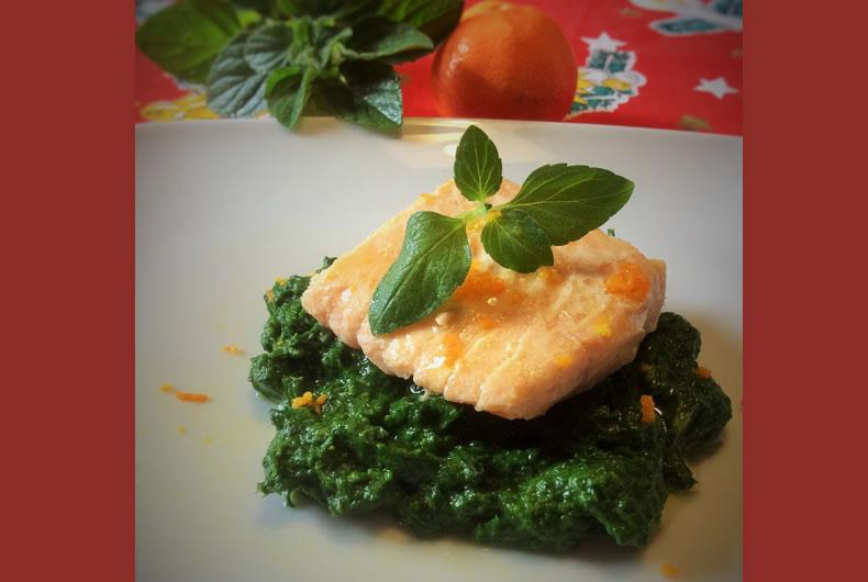 foto di un filetto di salmone impiattato su una crema di spinaci e decorato con foglie di menta