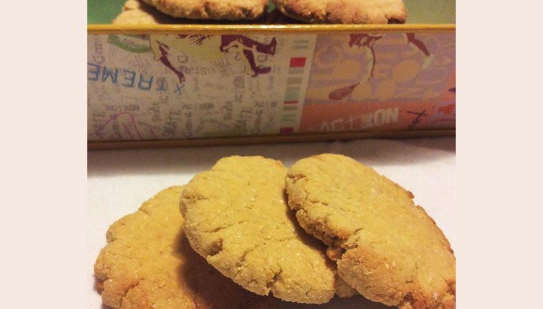 biscotti su una tavolo e dentro una scatola colorata di latta fatti con farina di cocco, ceci e zenzero