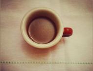 tazzina di caffè su tovaglia color crema