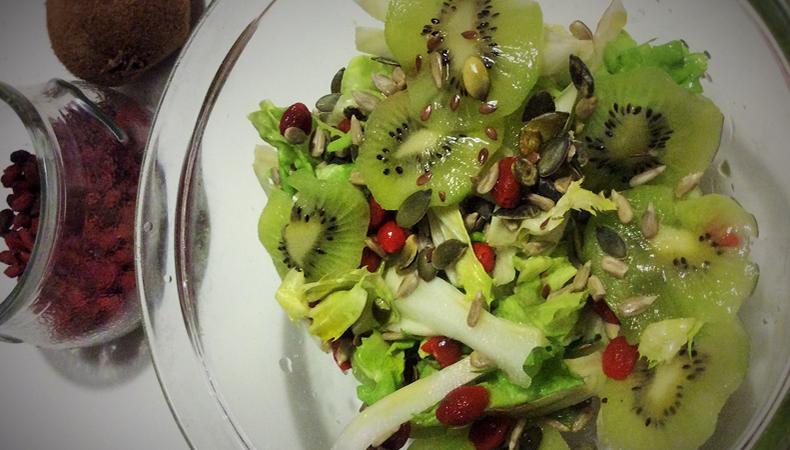 insalata verde con fette di kiwi e bacche di goji
