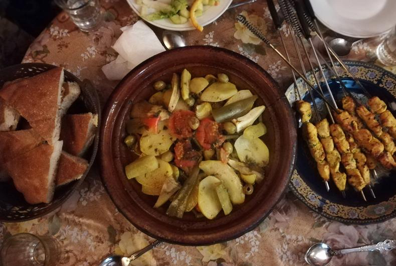 tavolo con tajina alle verdure con kebab di pollo e pane marocchino