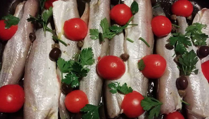 melu al forno con pomodori, capperi e olive nere